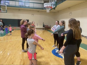 Participants learning how to play volleyball with members of the NC women's volleyball team.