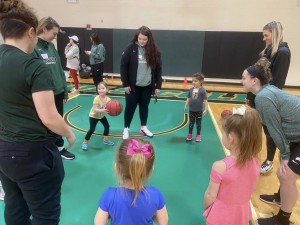 Young participants learn the basics of basketball from members of the NC women's basketball team.